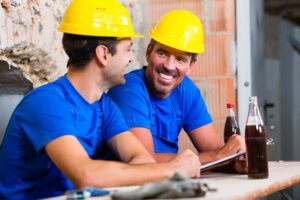 Builders having break on construction site sitting down drinking beverages